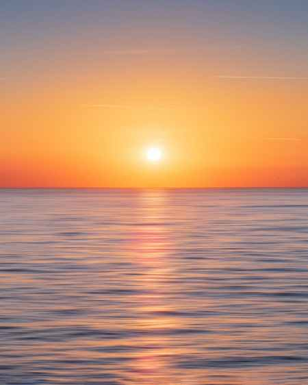 calm water with sun and orange sky